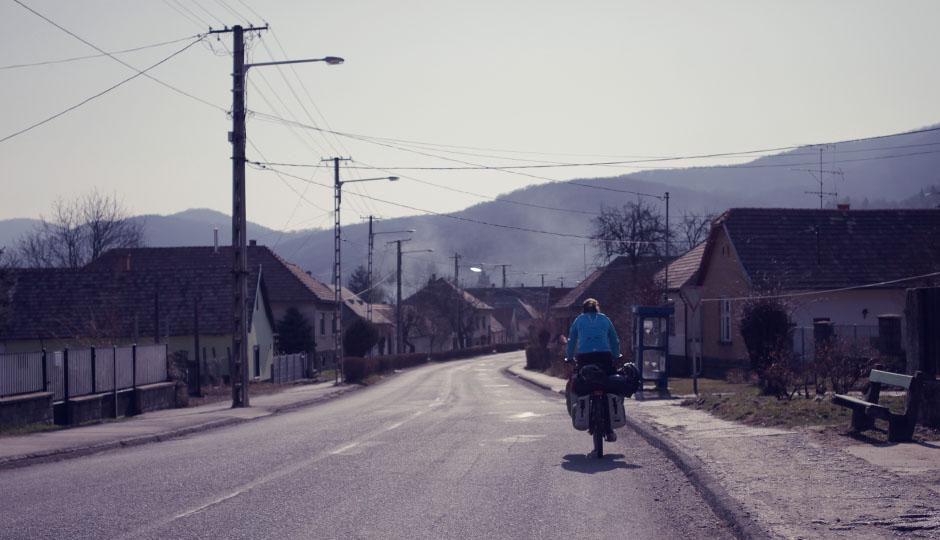 Durch ein ungarisches Dorf. Einstöckige Häuser in pastelligen Farben.