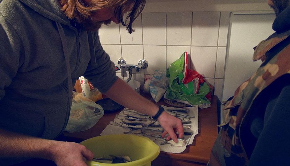 Die Jungs fritieren die frisch gefangenen Fische mit Mehl und Paprikapulver.