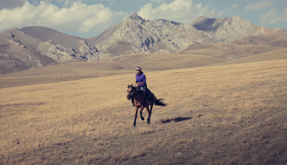 """Ein kirgisisches Sprichwort sagt, die """"Pferde sind die Flügel eines Mannes"""". Auch wenn ich eine Frau bin, ich fühle mich auch gerade, als könne ich über die endlose Weite hier fliegen."""