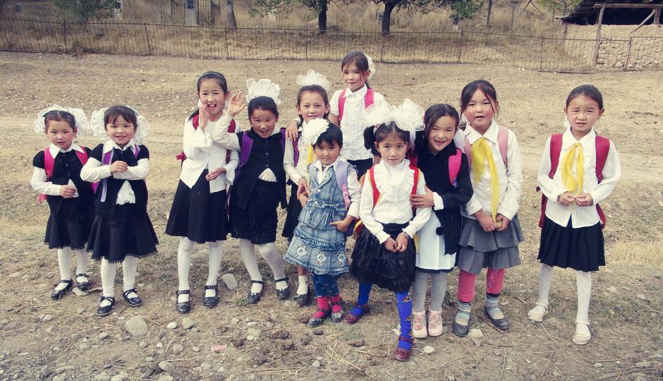 """Kirgisische Schuluniform: Schwar-weiß, Schürzen und übergroße """"Bommeln"""" in den Haaren"""