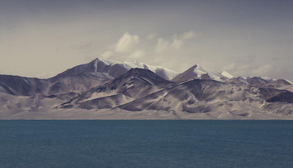Surreale Landschaft: Die Strasse führt vorbei an einem See, wo Schneeberge auf Sanddünen treffen