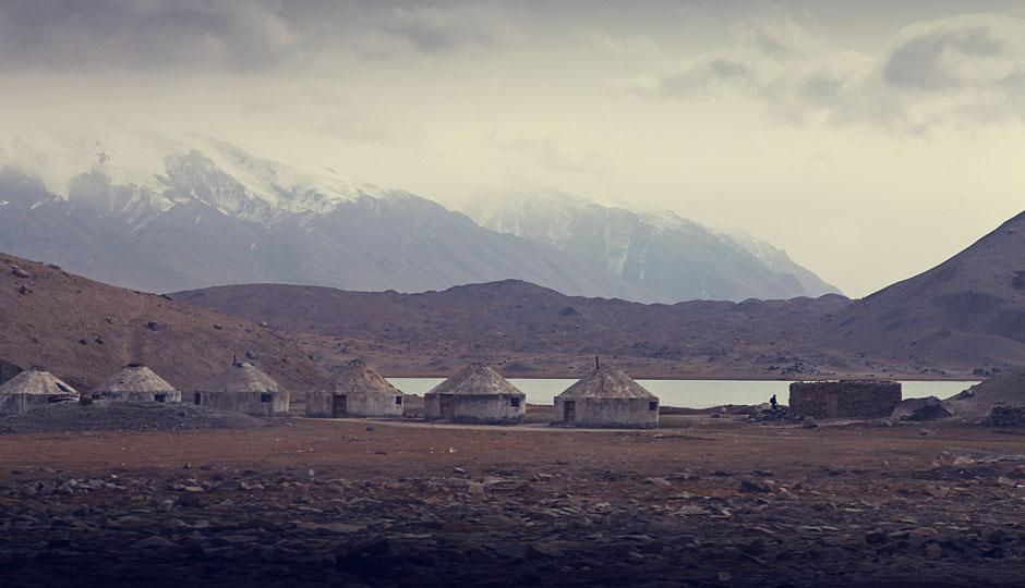 Jurten am Karakul See. Mit einer Höhe von 3600 m ist der See der höchstgelegene auf dem Pamirplateau. Zu den höchsten ganzjährig schneebedeckten Bergen, welche den See umgeben, gehören Muztagata (7509 m), Kongur Shan (7649 m) und Kongur Jiubie (7530 m).
